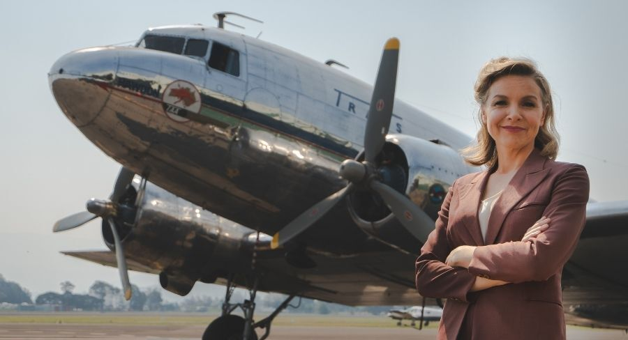 justine clarke australia come fly with me standing in front of plane